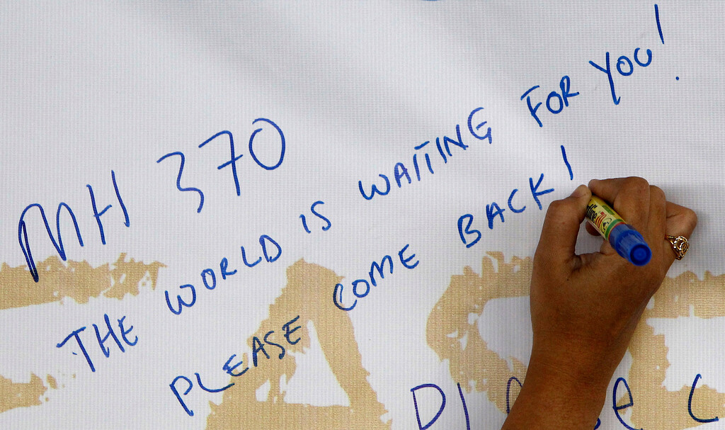 Description of . A woman writes a message for passengers aboard a missing Malaysia Airlines plane on a banner at Kuala Lumpur International Airport in Sepang, Malaysia, Wednesday, March 12, 2014. More than four days after the Malaysian jetliner went missing en route to Beijing, authorities acknowledged Wednesday they didn't know which direction the plane carrying 239 passengers was heading when it disappeared, vastly complicating efforts to find it. (AP Photo/Lai Seng Sin)
