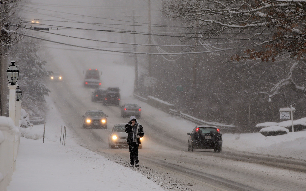 Description of . Traffic is sparse and the sidewalks impassable as a heavy snow falls in Pembroke, Mass., Wednesday morning, Feb. 5, 2014. The storm is expected to drop a foot or more of snow on some areas of the Massachusetts Wednesday making driving treacherous. (AP Photo/Stephan Savoia)