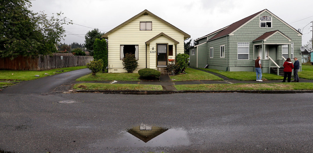Description of . This Monday, Sept. 23, 2013 photo shows the childhood home of Kurt Cobain, the late frontman of Nirvana, left, along an alley in Aberdeen, Wash. (AP Photo/Elaine Thompson)