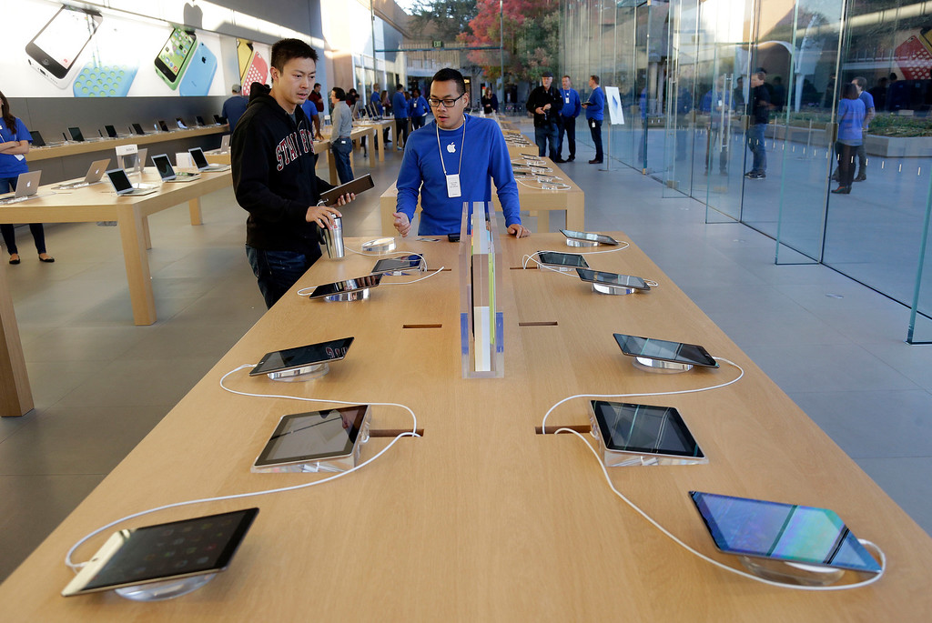 Description of . A customer looks at the new iPad Air on Friday, Nov. 1, 2013, in Stanford, Calif. Apple's iPad Air, a thinner, lighter and faster-running version of its previous large tablet computers, goes on sale Friday with a starting price of $499. (AP Photo/Marcio Jose Sanchez)