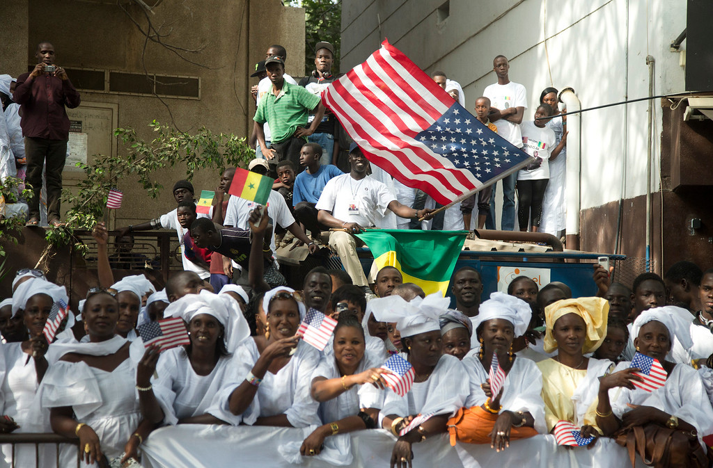 Description of . People line the motorcade route of U.S. President Barack Obama on his way to meet with Senegalese President Macky Sall at the Presidential Palace on Thursday, June 27, 2013, in Dakar, Senegal. Obama is visiting Senegal, South Africa, and Tanzania on a week long trip. (AP Photo/Evan Vucci)