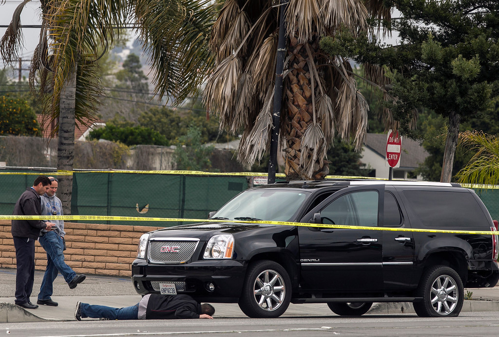 Description of . A police investigator looks under a disabled SUV left on Red Hill Ave. in Tustin, Calif., Tuesday, Feb. 19, 2013.  (AP Photo/Damian Dovarganes)