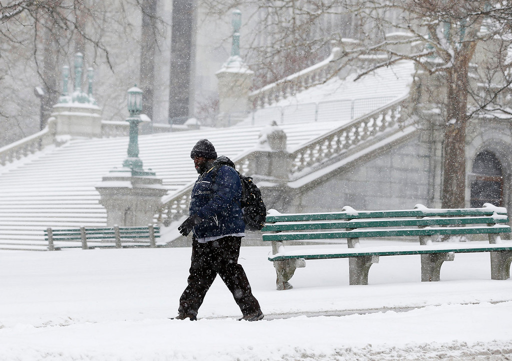Description of . A pedestrian walks through the snow outside the state Capitol on Thursday, Jan. 2, 2014, in Albany, N.Y. Up to 5 inches of snow have fallen in eastern New York early Thursday, but the National Weather Service said some areas from Buffalo to Albany could get up to 12 inches by the time the storm subsides on Friday. (AP Photo/Mike Groll)