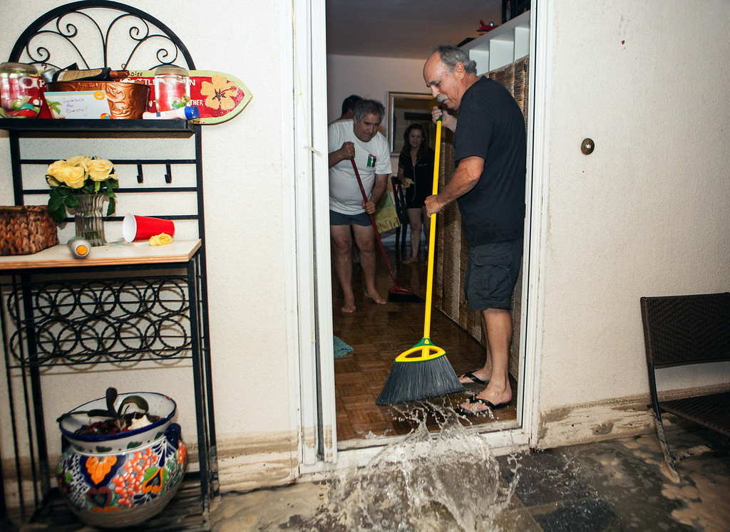 Description of . In this Tuesday, Aug. 26, 2014 photo, residents sweep out flood water from a home in Seal Beach, Calif. after high tide and large waves caused heavy flooding.  A low-lying street in the Southern California coastal community of Seal Beach has been inundated by a surge of rising seawater brought on by Hurricane Marie spinning off Mexico's Pacific coast. (AP Photo/Kevin Warn)
