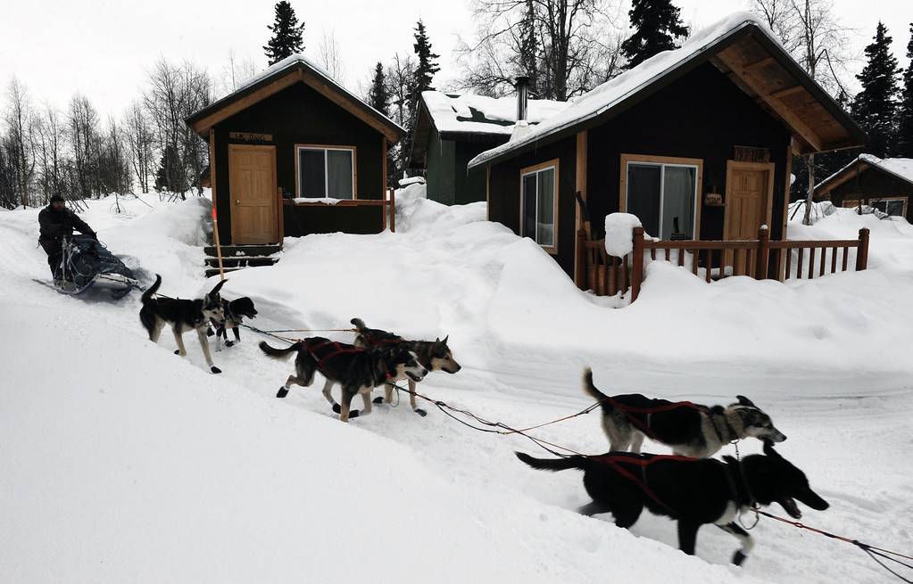 Description of . Robert Bundtzen drives his team past cabins at Winterlake Lodge at the Finger Lake checkpoint in Alaska during the Iditarod Trail Sled Dog Race on Monday, March 4, 2013. (AP Photo/The Anchorage Daily News, Bill Roth)