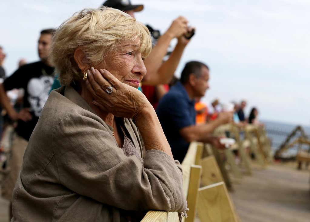 Description of . A woman looks on as people gather on the Seaside Park boardwalk to look at the destruction left behind after a massive fire that started a day earlier, Friday, Sept. 13, 2013, in Seaside Park, N.J.  (AP Photo/Julio Cortez)