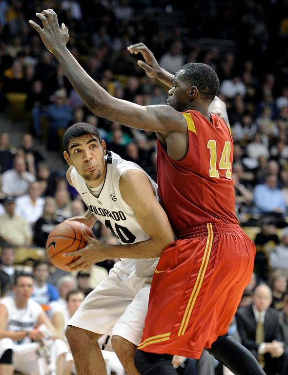 Description of . University of Colorado's Josh Scott drives past DeWayne Dedmon during a game against the University of Southern California on Thursday, Jan. 10, at the Coors Event Center on the CU campus in Boulder. Jeremy Papasso/Daily Camera