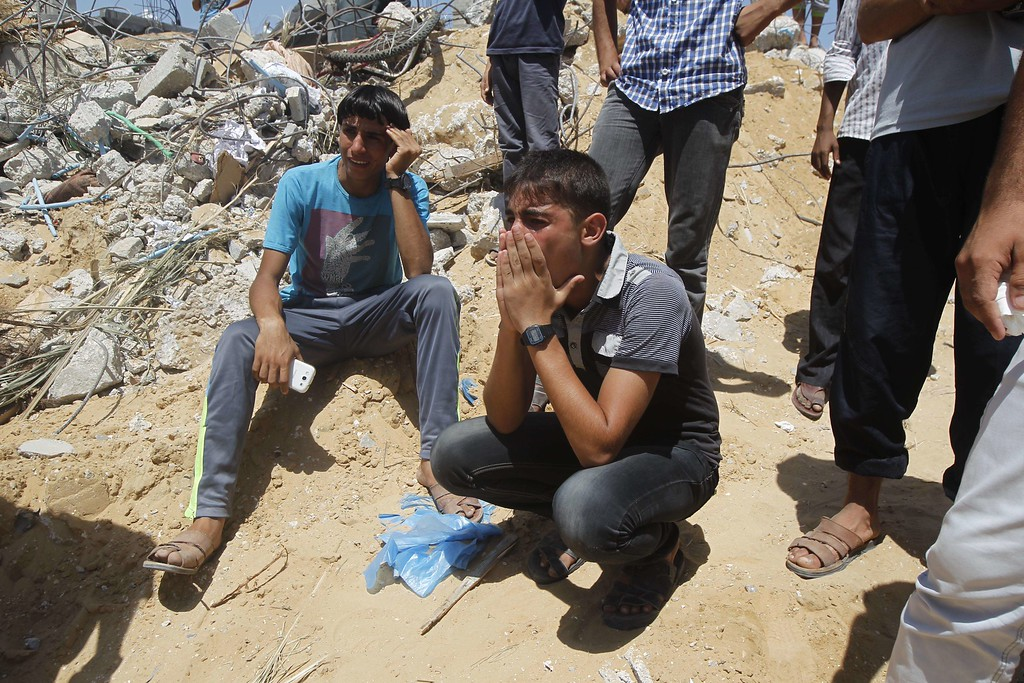 Description of . Palestinian youths weep as they watch rescue workers on July 30, 2014 removing the body of a dead child from under the rubble of the Duheir family home which was destroyed in an Israeli air strike the previous day in Rafah in the southern Gaza Strip.  At least 54 people died in Israeli strikes across Gaza on July 30, including 16 killed when shells hit a UN school, sending the Palestinian toll from 23 days of fighting to more than 1,280. AFP PHOTO/ SAID  KHATIB/AFP/Getty Images