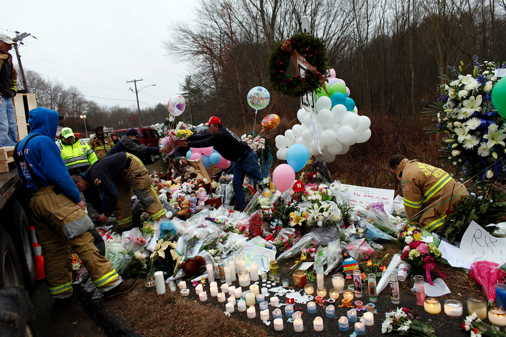 Description of . Firefighters and other volunteers reorganize a memorial for shooting victims near Sandy Hook Elementary School before erecting a shelter over it, Sunday, Dec. 16, 2012 in Newtown, Conn.  A gunman walked into Sandy Hook Elementary School in Newtown Friday and opened fire, killing 26 people, including 20 children. (AP Photo/Jason DeCrow)