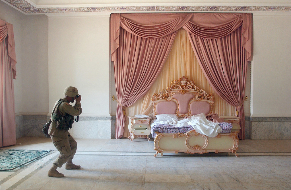 Description of . US Army Sergeant Craig Zentkovich from Connecticut of the 1st Brigade Combat Team photographs a pink bedroom at Saddam Hussein\'s presidential palace 13 April 2003. (Romeo Gacad/AFP/Getty Images)