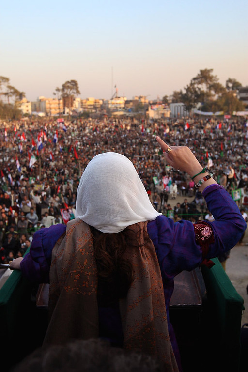 Description of . RAWALPINDI, PAKISTAN - DECEMBER 27: Former Pakistani Prime Minister Benazir Bhutto addresses supporters at a campaign rally minutes before being assassinated in a bomb attack on December 27, 2007 in Rawalpindi, Pakistan.  (Photo by John Moore/Getty Images)