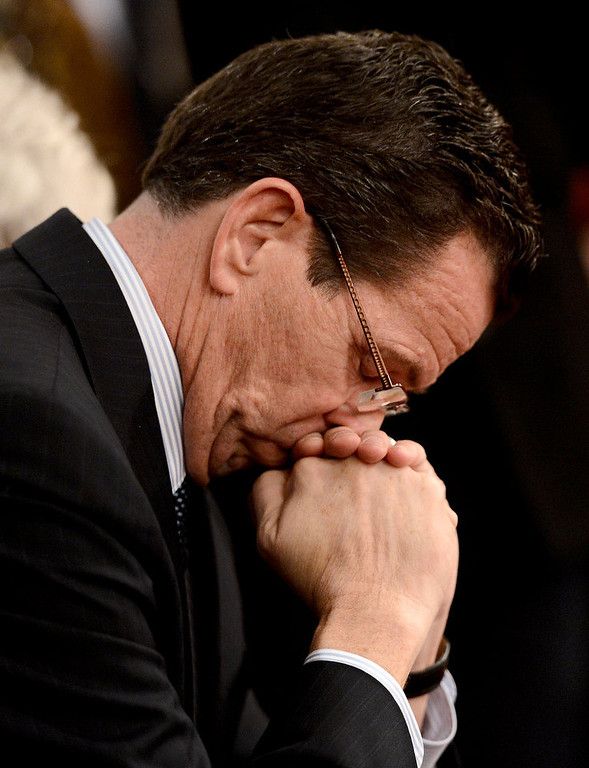 Description of . Connecticut Gov. Dannel Malloy bows his head during a moment of silence during a vigil service for victims of the Sandy Hook Elementary School shooting, at the St. Rose of Lima Roman Catholic Church in Newtown, Conn. Friday, Dec. 14, 2012.  (AP Photo/Andrew Gombert, Pool)