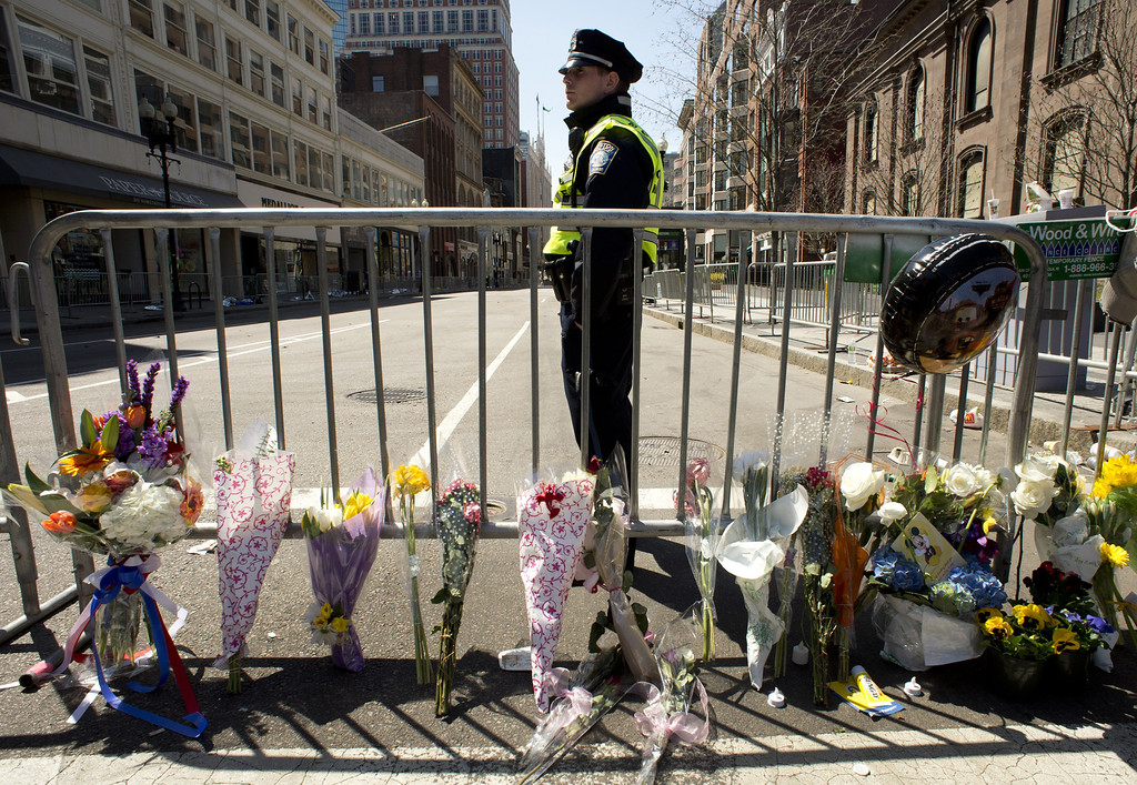 Description of . A Boston police officer stands guard at a memorial site at Boylston and Arlington streets along the course of the Boston Marathon on April 16, 2013, a few blocks from where two explosions struck near the finish line of the Boston Marathon on April 15. The explosives used in the Boston Marathon bombings were likely homemade devices full of nails and metal fragments designed to cause widespread injury, according to initial reports. A day after an attack that left three dead and more than 170 wounded, the FBI and Boston police declined to reveal details of their probe, or whether they suspected the assault was linked to foreign or domestic extremists.   DON EMMERT/AFP/Getty Images