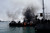Smoke rises from fires set by protestors in an attempt to block boats from docking and disrupt traffic at the port on the Suez Canal to demonstrate after the announcement of the final verdict in the case of the Port Said football massacre, on March 9, 2013, in Port Said, Egypt. (Photo by Ed Giles/Getty Images).
