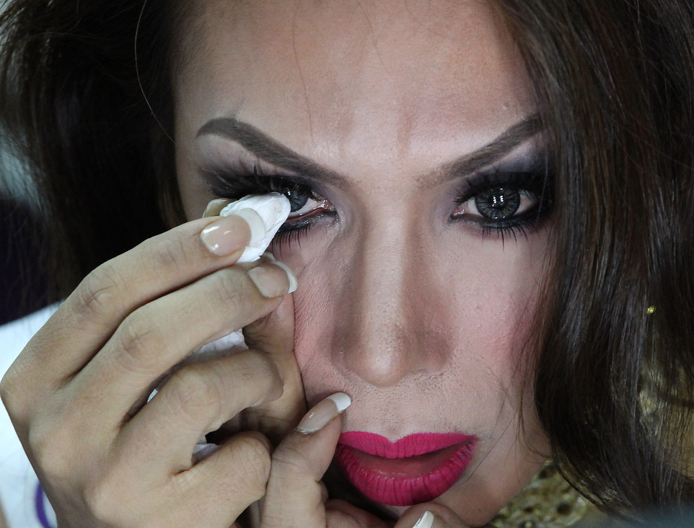 Description of . Andrea Justine Aliman of the Philippines applies makeup on her eye during a backstage photo session at the Miss International Queen 2013 transgender beauty pageant in Pattaya, southeastern Thailand Friday, Nov. 1, 2013.  (AP Photo/Apichart Weerawong)