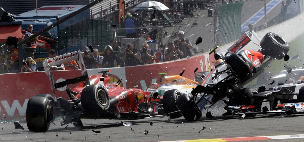 Description of . In this Sept. 2, 2012 file photo, Ferrari driver Fernando Alonso of Spain, left, crashes with McLaren Mercedes driver Lewis Hamilton of Britain, airborne right,  during the first lap of the Belgium Formula One Grand Prix in Spa-Francorchamps circuit, Belgium. (AP Photo/Luca Bruno, File)