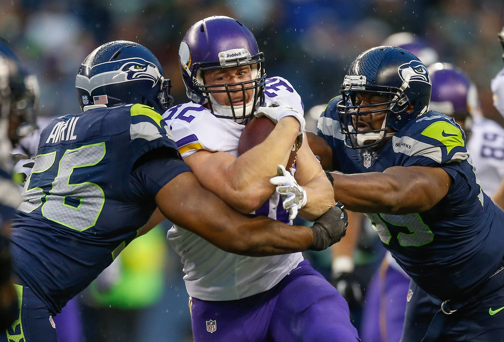 Description of . Running back Toby Gerhart #32 of the Minnesota Vikings rushes against defensive end Cliff Avril #56 of the Seattle Seahawks at CenturyLink Field on November 17, 2013 in Seattle, Washington. The Seahawks defeated the Vikings 41-20.  (Photo by Otto Greule Jr/Getty Images)