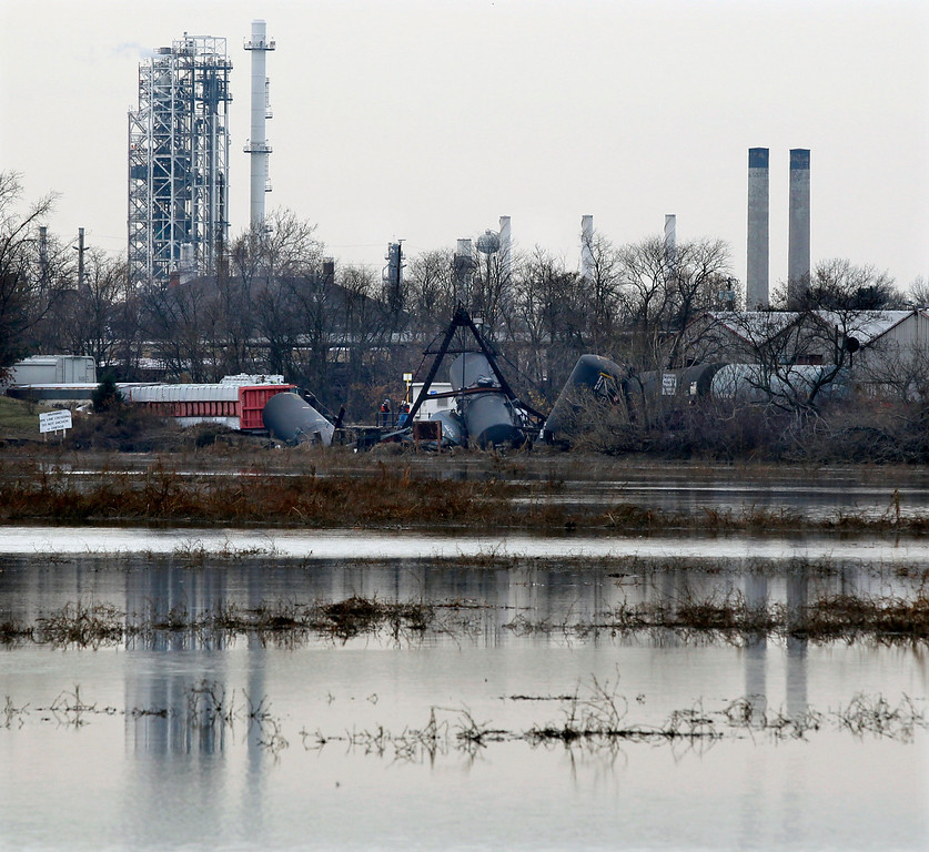 Description of . Derailed freight train cars lie scattered near the tracks in Paulsboro, N.J., Friday, Nov. 30, 2012 with a refinery in the background. The freight train derailed on a railroad bridge that has had problems before, toppling tanker cars partially into a creek and causing a leak of hazardous gas that was blamed for sickening dozens of people, authorities said. (AP Photo/Mel Evans)