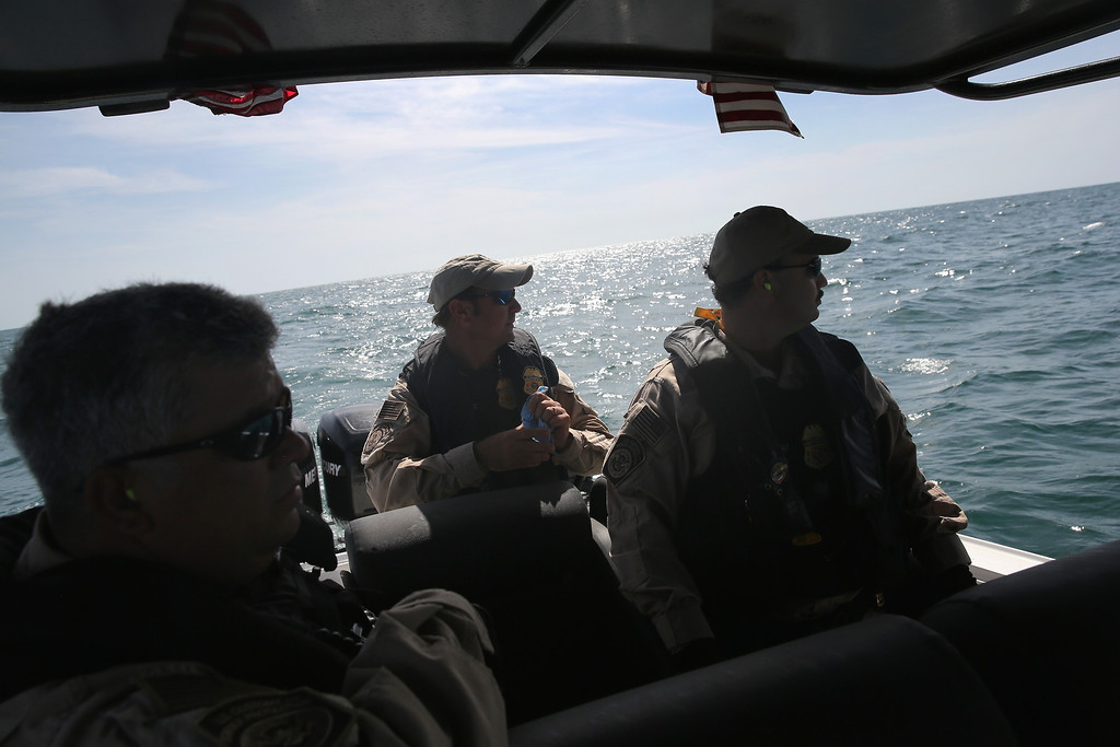 Description of . PORT ISABEL, TX - APRIL 12:  A boat crew from the U.S. Office of Air and Marine (OAM) looks towards a suspicious boat just across the Mexican border in the Gulf of Mexico on April 12, 2013 near Port Isabel, Texas. The crew patrols coastline waters near the U.S.-Mexico border searching for drug smugglers as well as illegal immigrants, which come across from Mexico near the mouth of the Rio Grande River. The Midnight Express interceptor is a 39 foot 900 horsepower craft capable of chasing smugglers down at 55 knots (63 mph). OAM units also push back illegal fishing boats out of U.S. waters.  (Photo by John Moore/Getty Images)