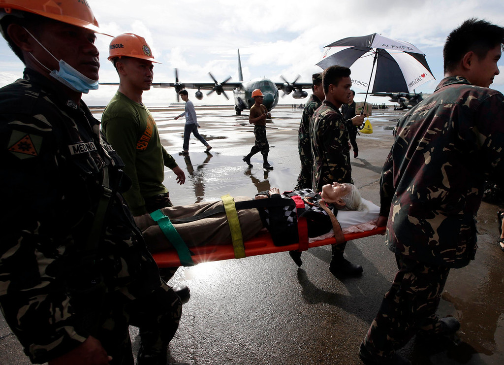 Description of . An injured typhoon survivor is carried on a stretcher prior to being airlifted in a military transport plane Wednesday Nov. 13, 2013 from the damaged Tacloban airport  at Tacloban city, Leyte province in central Philippines. Typhoon Haiyan, one of the strongest storms on record, slammed into central Philippine provinces Friday, leaving a wide swath of destruction and thousands of people dead. (AP Photo/Bullit Marquez)