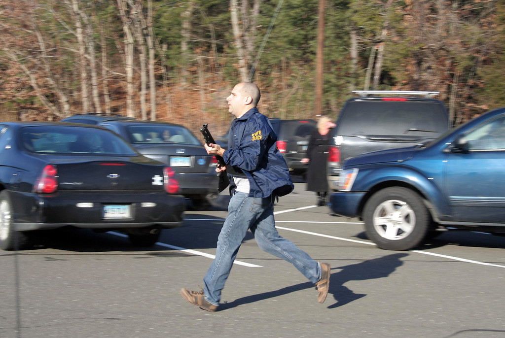 Description of . In this photo provided by the Newtown Bee, a state police officer runs outside of Sandy Hook Elementary School in Newtown, Conn., where authorities say a gunman opened fire, killing 26 people, including 20 children, Friday, Dec. 14, 2012. (AP Photo/Newtown Bee, Shannon Hicks)
