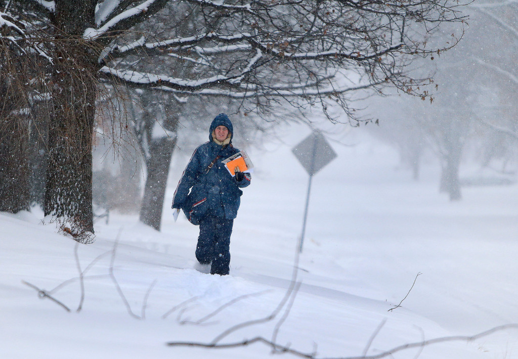 Description of . A letter carrier walks through the snow while delivering mail Tuesday, Feb. 4, 2014, in Topeka, Kan. (AP Photo/Topeka Capital-Journal, Chris Neal)