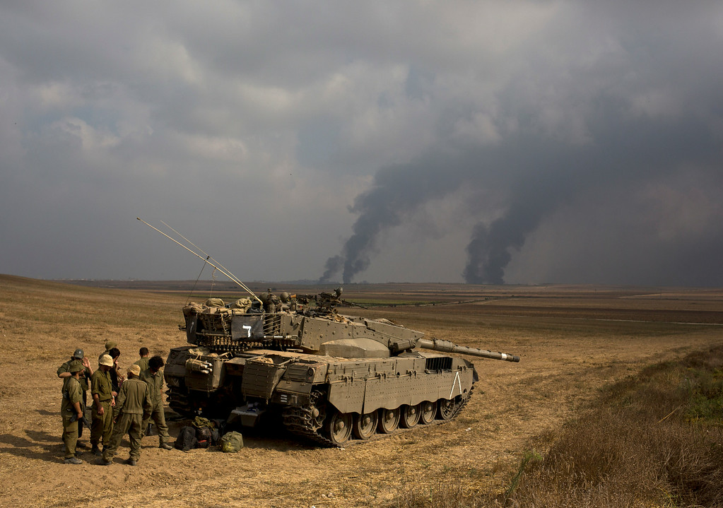 Description of . Israeli soldiers stand behind a tank as heavy smoke rises from the Gaza Strip Tuesday, July 22, 2014. Israeli airstrikes pummeled a wide range of targets in the Gaza Strip on Tuesday as the U.N. chief and the U.S. secretary of state began an intensive effort to end more than two weeks of fighting that has killed hundreds of Palestinians and tens of Israelis. (AP Photo/Dusan Vranic)