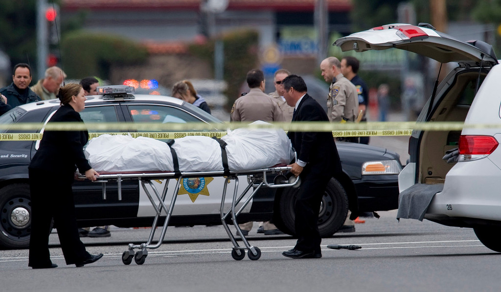 Description of . The Orange County coroner's office wheels a body to a waiting van in Orange, Calif., Tuesday, Feb. 19, 2013. (AP Photo/The Orange County Register, Mark Rightmire)