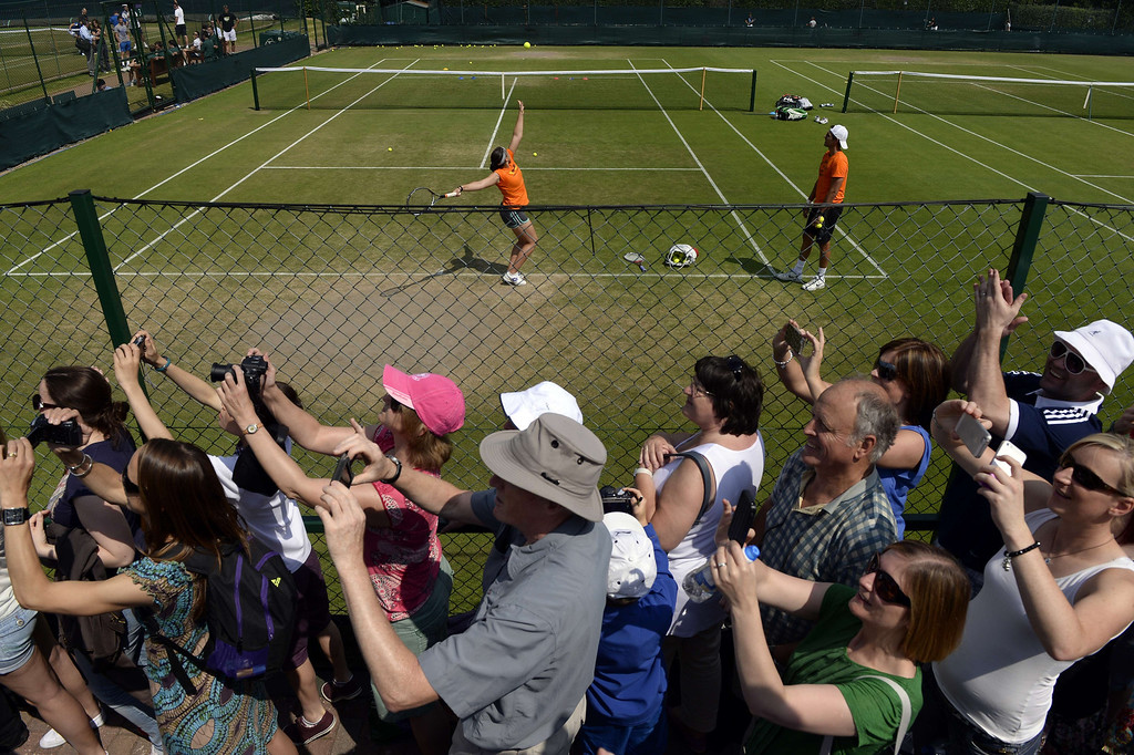 Description of . Spectators turn to look at Britain\'s Andy Murray as France\'s Marion Bartoli trains in the background on day eleven of the 2013 Wimbledon Championships tennis tournament at the All England Club in Wimbledon, southwest London, on July 5, 2013, ahead of the women\'s singles final match on July 6. ADRIAN DENNIS/AFP/Getty Images