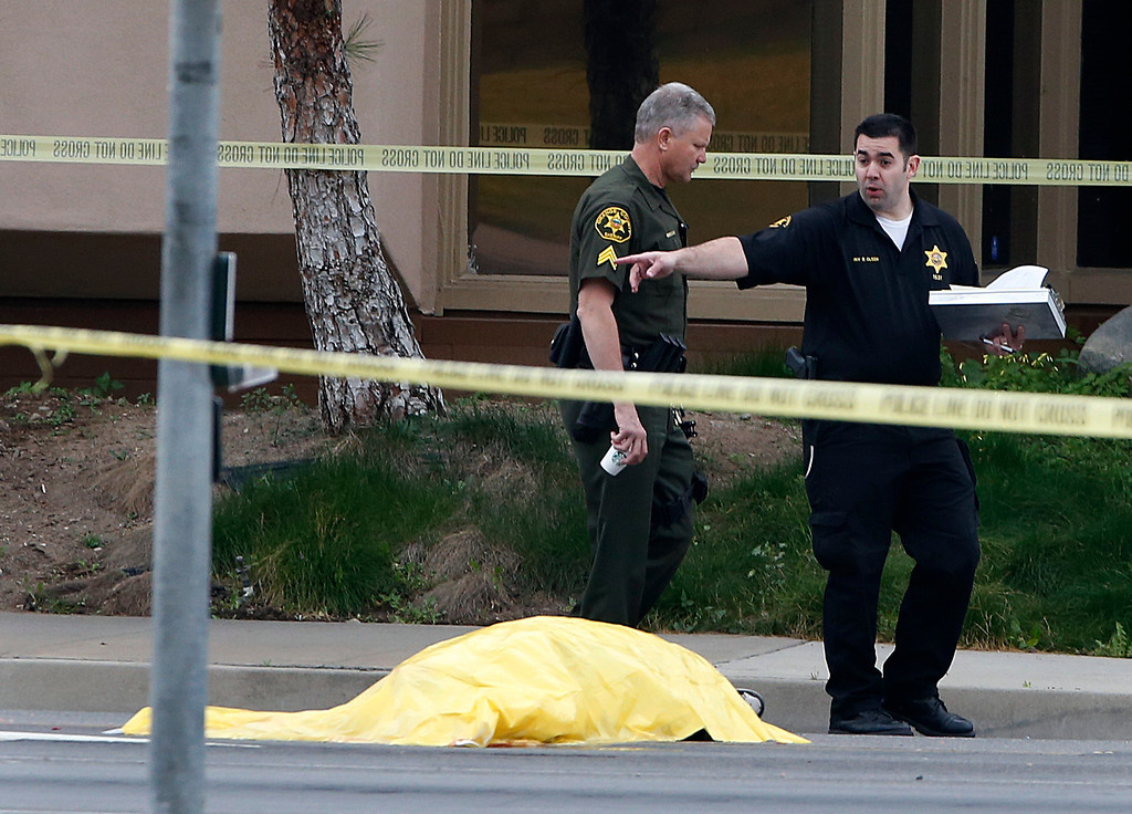 Description of . Investigators walk past a tarp covered body in Orange, Calif., Tuesday, Feb. 19, 2013. Police say a chaotic 25-minute shooting spree through Orange County left a trail of dead and injured victims before the shooter killed himself. Orange County sheriff\'s spokesman Jim Amormino say there are at least six crime scenes with three people, including the suspected gunman, dead and several others wounded. Tustin police Supervisor Dave Kanoti said the shootings started with an apparent carjacking just after 5 a.m. Tuesday in an unincorporated Ladera Ranch area of Orange County. (AP Photo/Jae C. Hong)