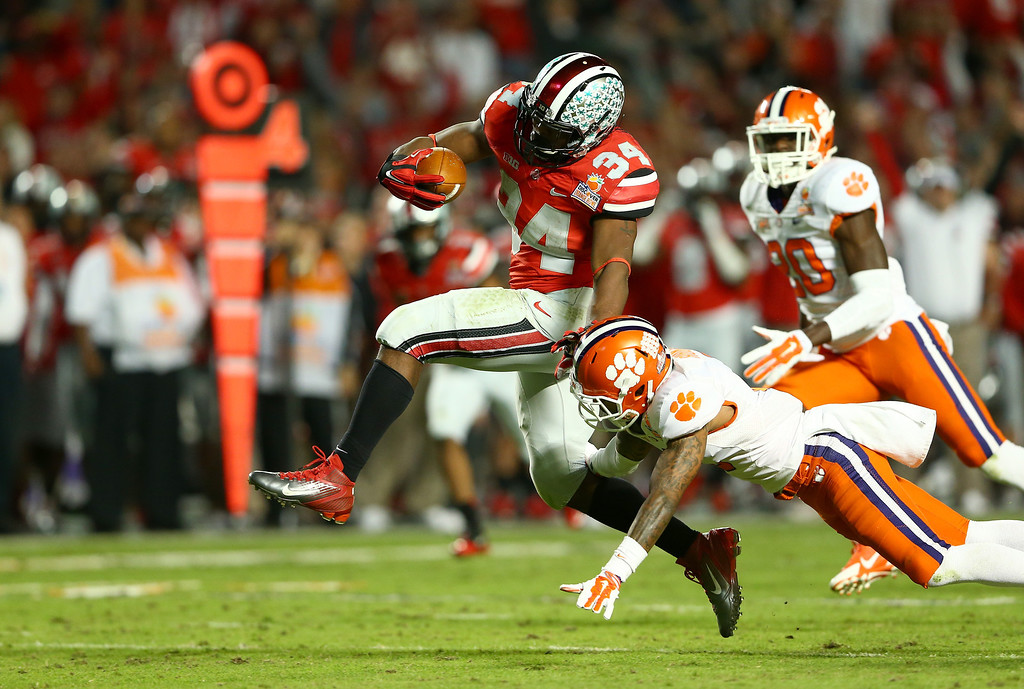 Description of . MIAMI GARDENS, FL - JANUARY 03:  Carlos Hyde #34 of the Ohio State Buckeyes runs with the ball in the third quarter against the Clemson Tigers during the Discover Orange Bowl at Sun Life Stadium on January 3, 2014 in Miami Gardens, Florida.  (Photo by Streeter Lecka/Getty Images)
