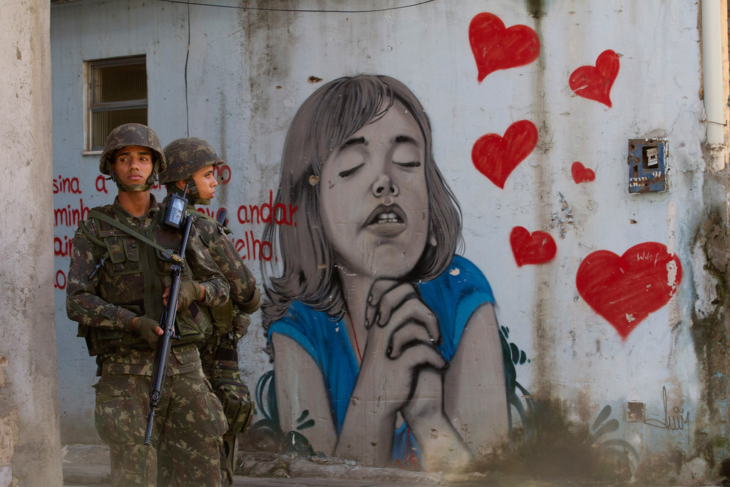 Description of . Army soldiers stand next to a graffiti during an operation to occupy the Mare slum complex in Rio de Janeiro, Brazil, Saturday, April 5, 2014. More than 2,000 Brazilian Army soldiers moved into the Mare slum complex early Saturday in a bid to improve security and drive out the heavily armed drug gangs that have ruled the sprawling slum for decades. (AP Photo/Silvia Izquierdo)