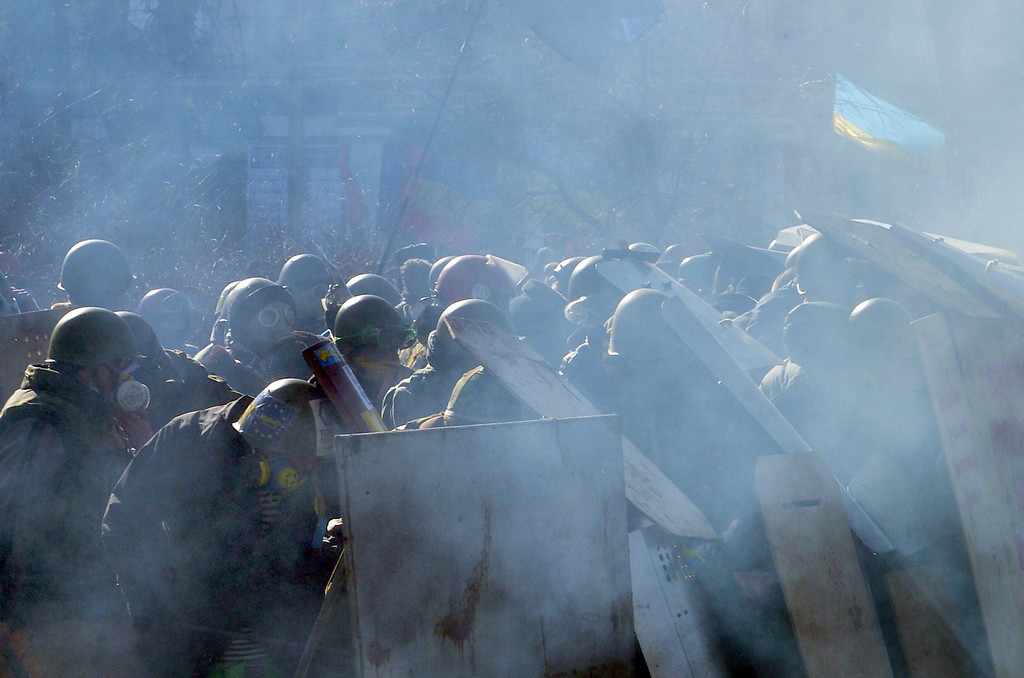 Description of . Anti-government protesters shield themselves during clashes with riot police in front of the Parliament in central Kiev on February 18, 2014.    