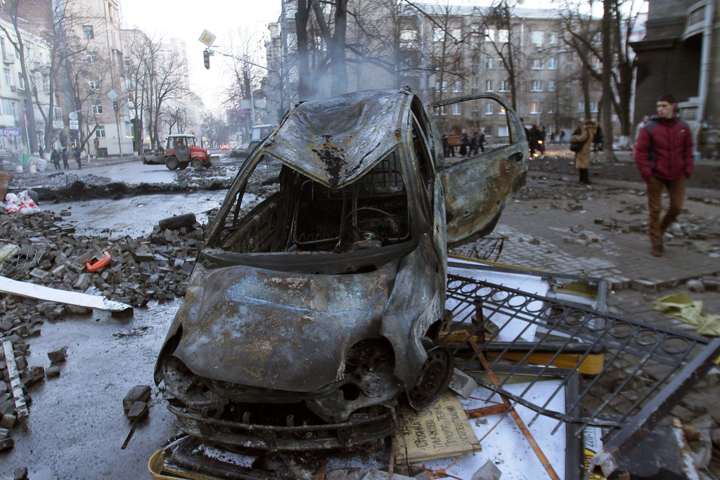 Description of . Burnt out vehicles remain after protesters clashes with police in Kiev on February 18, 2014. AFP PHOTO/ ANATOLII  BOIKO/AFP/Getty Images