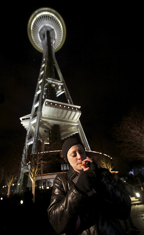 Description of . Robyn Bowen of Seattle Washington smokes marijuana underneath the Space Needle shortly after a law legalizing the recreational use of  marijuana took effect on December 6, 2012 in Seattle, Washington.  Voters approved an initiative to decriminalize the recreational use of marijuana making it one of the first states to do so. (Photo by Stephen Brashear/Getty Images)