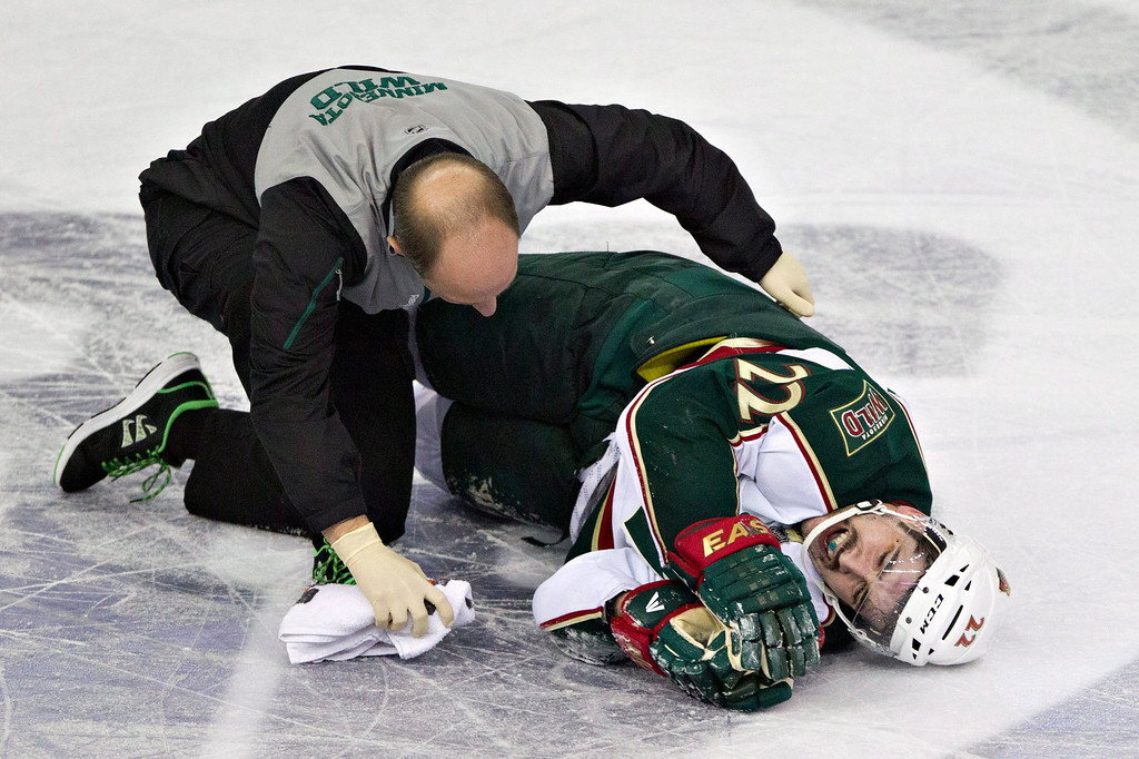 . Minnesota Wild\'s Cal Clutterbuck is tended to by a trainer after being hit by Edmonton Oilers Taylor Hall during third period NHL hockey action in Edmonton, Alberta, on Thursday Feb. 21, 2013. (AP Photo/THE CANADIAN PRESS,Jason Franson)