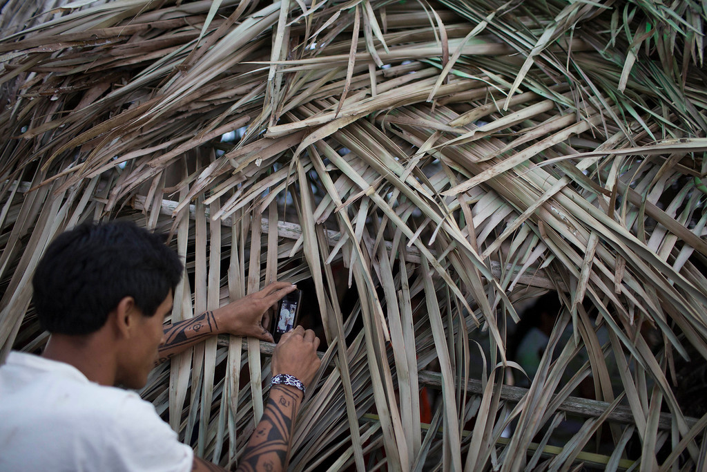 Description of . A man uses a phone to make a picture of those inside a traditional indigenous home during the indigenous games in Cuiaba, Brazil, Tuesday, Nov. 12, 2013.  (AP Photo/Felipe Dana)