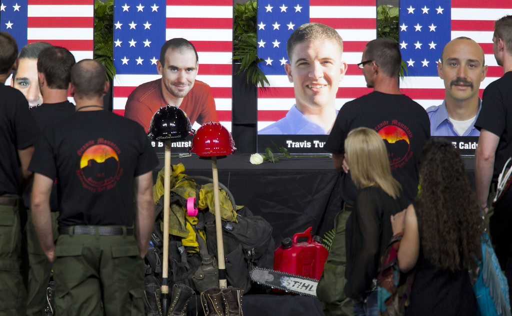 Description of . Photos of some of the 19 fallen firefighters line the front of the stage before a memorial service at Tim's Toyota Center July 9, 2013 in Prescott Valley, Arizona. (Photo by  David Wallace-Pool/Getty Images)