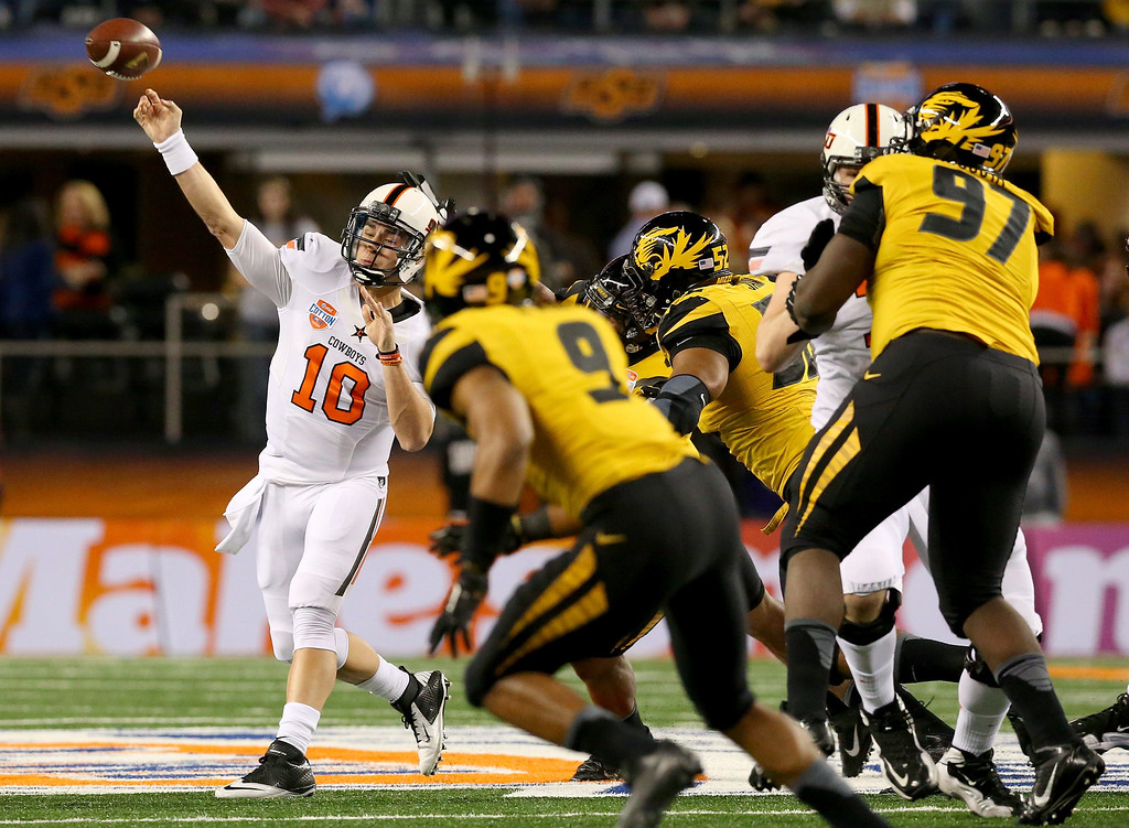 Description of . ARLINGTON, TX - JANUARY 03:  Quarterback Clint Chelf #10 of the Oklahoma State Cowboys passes the ball in the first half against the Missouri Tigers during the AT&T Cotton Bowl on January 3, 2014 in Arlington, Texas.  (Photo by Ronald Martinez/Getty Images)