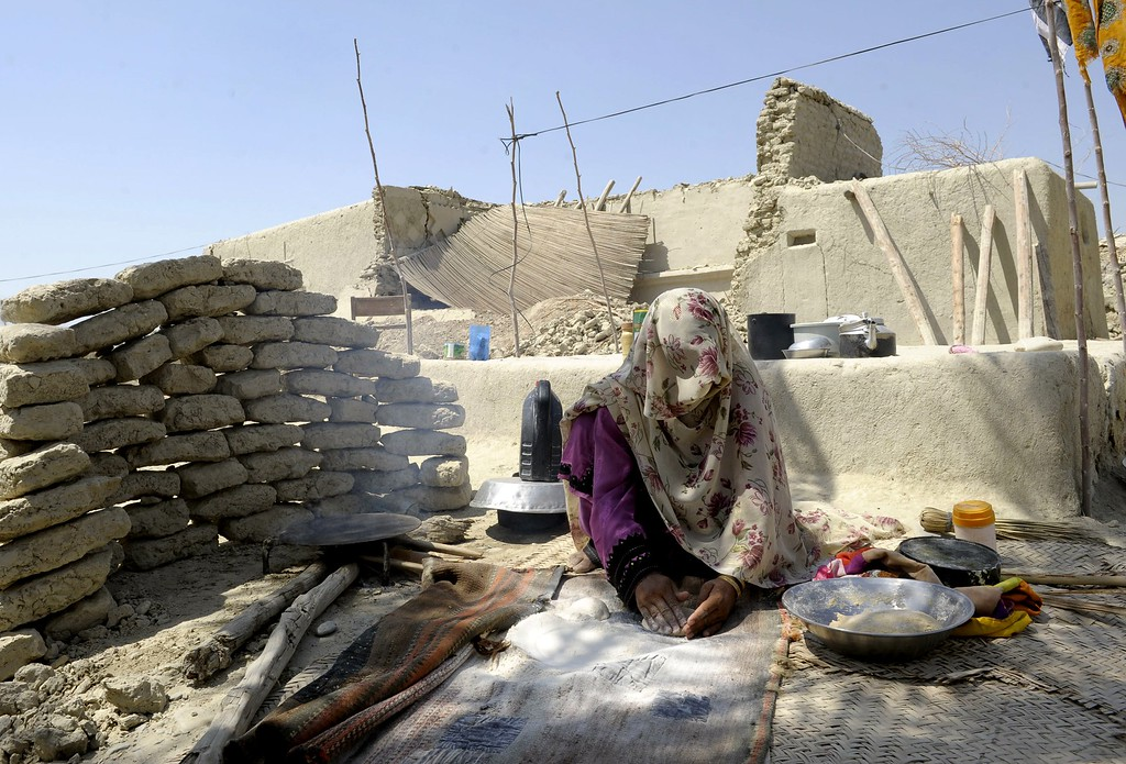 Description of . A Pakistani earthquake survivor prepares bread alongside her partially-collapsed mud house at Labach area, in the earthquake-devastated district of Awaran on September 26, 2013. Tens of thousands of survivors of Pakistan's earthquake waited for help in soaring temperatures on September 26 as the death toll rose to nearly 350 and anger grew at the slow pace of government aid. More than 100,000 people made homeless by a 7.7-magnitude quake spent a second night in the open or under makeshift shelters as response teams struggled to reach the remote region in the southwestern province of Baluchistan.  AFP PHOTO / Banaras KHAN/AFP/Getty Images