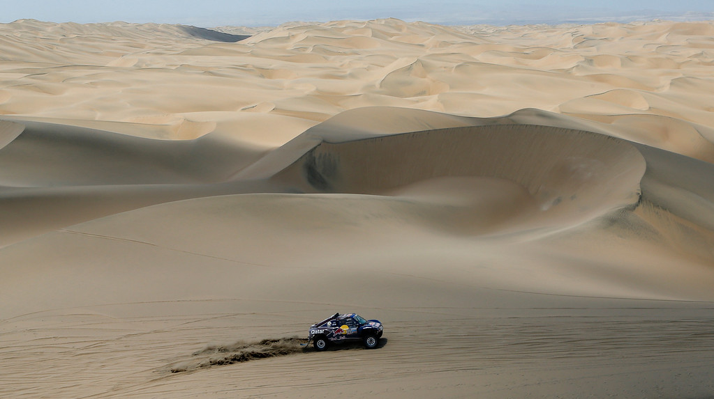 Description of . Driver Carlos Sainz of Spain and German co-driver Timo Gottschalk compete in the 3nd stage of the 2013 Dakar Rally from Pisco to Nazca, Peru, Monday, Jan. 7, 2013. The race finishes in Santiago, Chile, on Jan. 20. (AP Photo/Victor R. Caivano)
