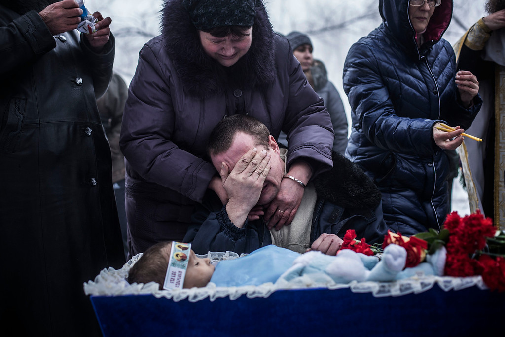 Description of . Vladimir Bovrichev, 30, cries next to the body of his son Artiam, 4, killed in a Ukrainian army artillery strike, during his funeral in Kuivisevsky district on the outskirts of Donetsk, eastern Ukraine, Tuesday, Jan. 20, 2015. At least three civilians were killed in shelling Tuesday in eastern Ukraine as fighting continued between government and rebel forces in the separatist-held city of Donetsk. (AP Photo/Manu Brabo)