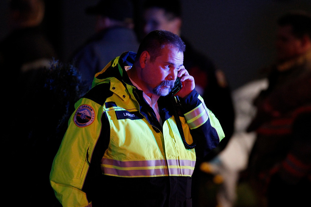 Description of . A paramedic talks on the phone outside Clackamas Town Center in Clackamas, Ore., where a shooting occurred Tuesday, Dec. 11, 2012. A gunman opened fire in the Portland, Ore., area shopping mall Tuesday, killing at least one person and wounding an unknown number of others, sheriff's deputies said. (AP Photo/The Oregonian, Bruce Ely)