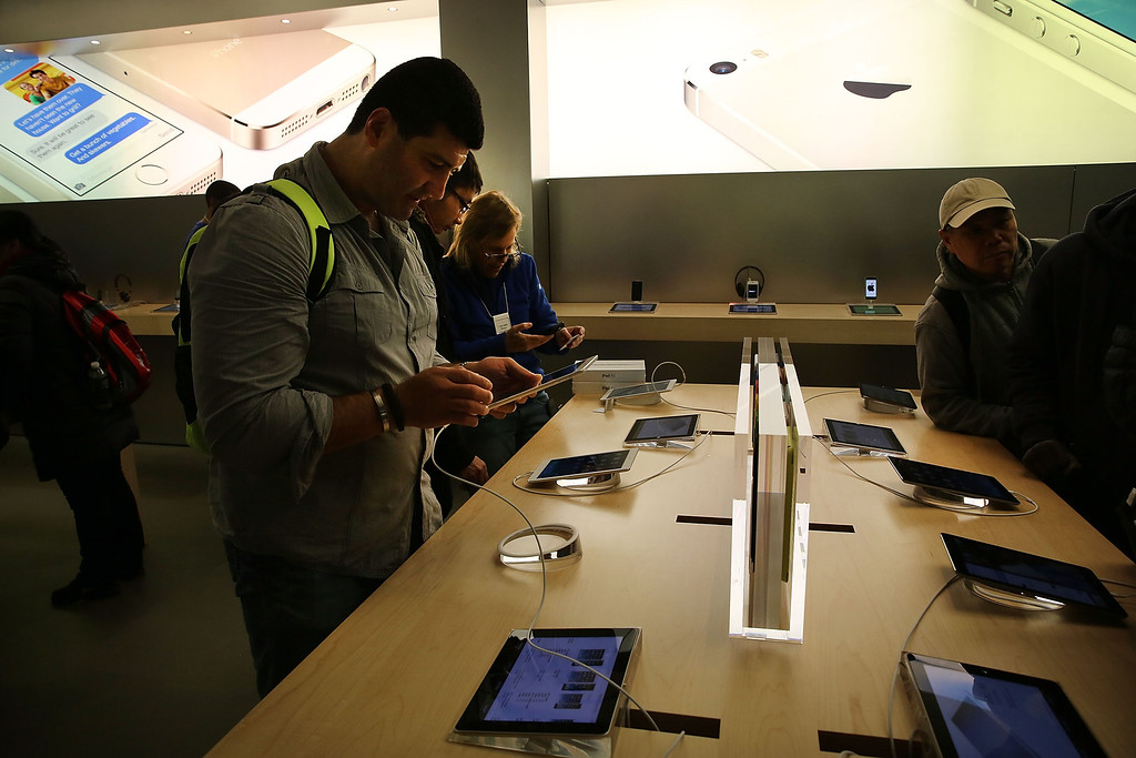 Description of . People try the new Apple iPad Air at the Apple Store on November 1, 2013 in New York City.   (Photo by Spencer Platt/Getty Images)