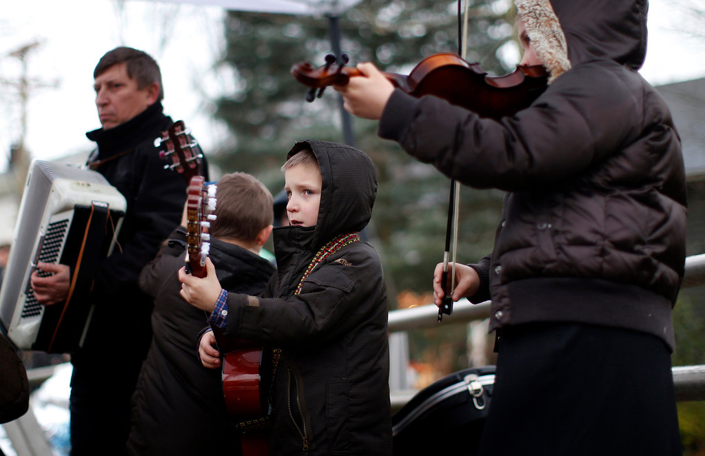 Description of . The Kulish family from New Britain, Connecticut, plays Christmas carols near a makeshift memorial close to Sandy Hook Elementary School for the victims of a school shooting in Newtown, Connecticut Sunday December 16, 2012. Twelve girls, eight boys and six adult women were killed in the shooting on Friday at the Sandy Hook Elementary School in Newtown.  REUTERS/Mike Segar