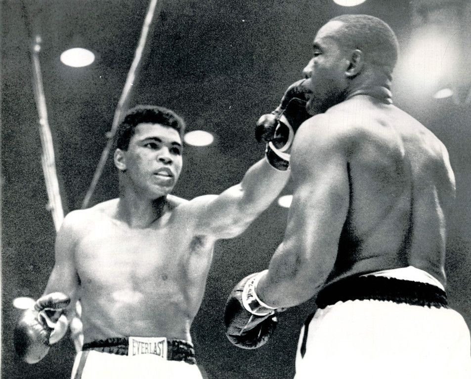 Description of . Challenger Cassius Clay pokes a fast left jab to the face of Sonny Liston during their championship heavyweight fight in Miami Beach, Fla. tonight.  Clay used the in and out tactics to gain a TKO in the seventh round after Liston strained a shoulder and suffered a bad gash under the left eye. 1964   AP Wirephoto