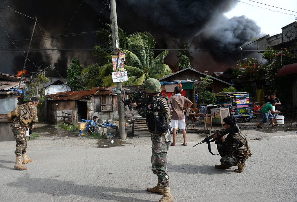 Description of . Philippine soldiers aim their rifles at enemy positions during a fire fight with Muslim rebels in Zamboanga City in southern island of Mindanao on September 12, 2013.  TED ALJIBE/AFP/Getty Images