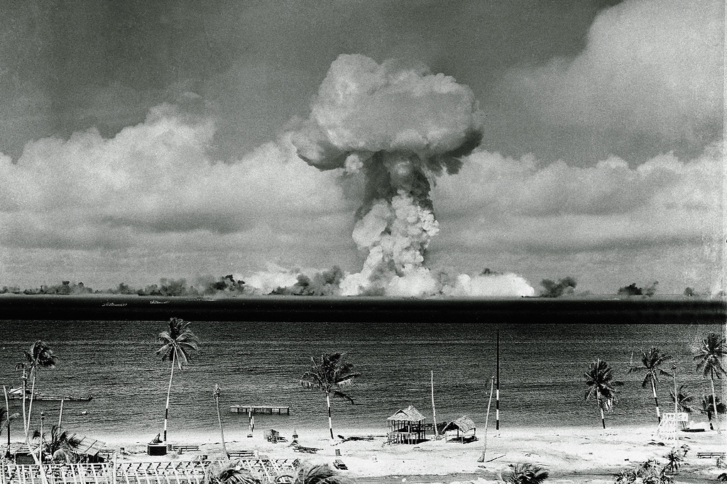 Description of . The mushroom cloud of an atom bomb rises among abandoned ships in Bikini lagoon on July 1, 1946 after the bomb was dropped from the Super Fortress