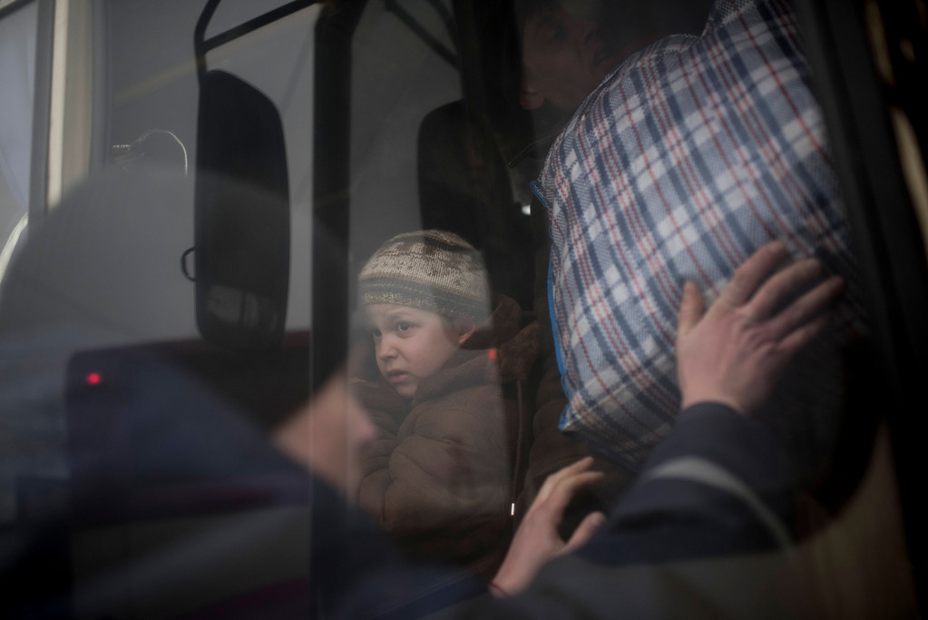 Description of . A Ukrainian boy looks through a window of a bus near Artemivsk, eastern Ukraine,  Thursday Feb. 5, 2015, as people are evacuated from Debaltseve. Fighting between Russia-backed separatists and Ukrainian forces in eastern Ukraine surged in January, raising the death toll to over 5,300 people killed since April. In a new push for peace, the leaders of France and Germany headed Thursday to Kiev and Moscow with a proposal to end the fighting in eastern Ukraine. (AP Photo/Evgeniy Maloletka)