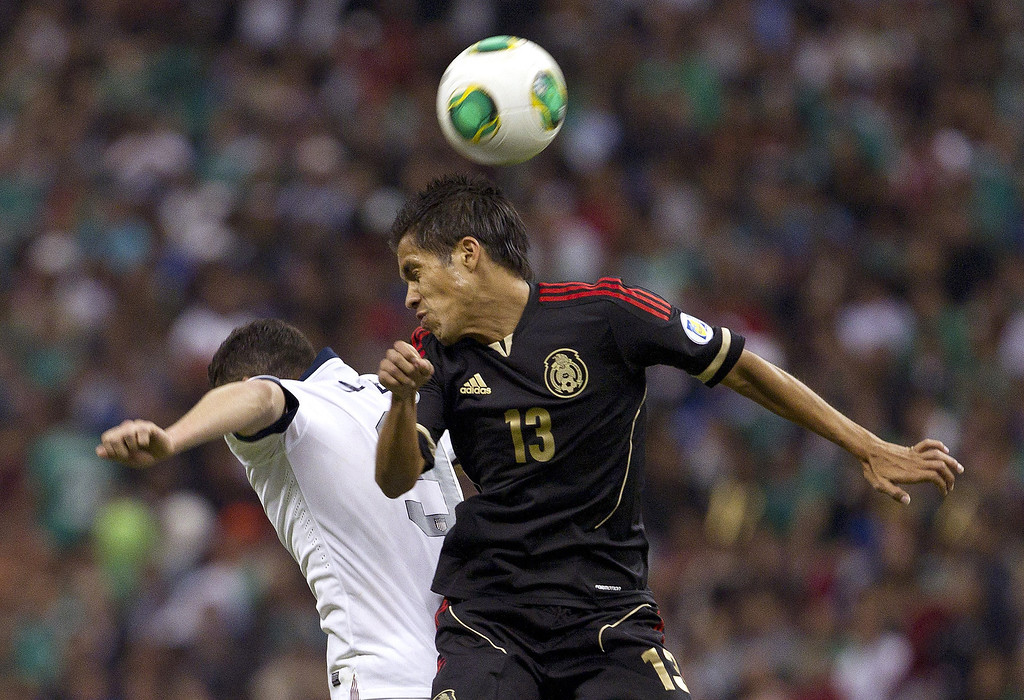 Description of . Mexico's Severo Meza, right, and United States' Herculez Gomez fight for the ball during a 2014 World Cup qualifying match at the Aztec stadium in Mexico City, Tuesday, March 26, 2013. (AP Photo/Christian Palma)